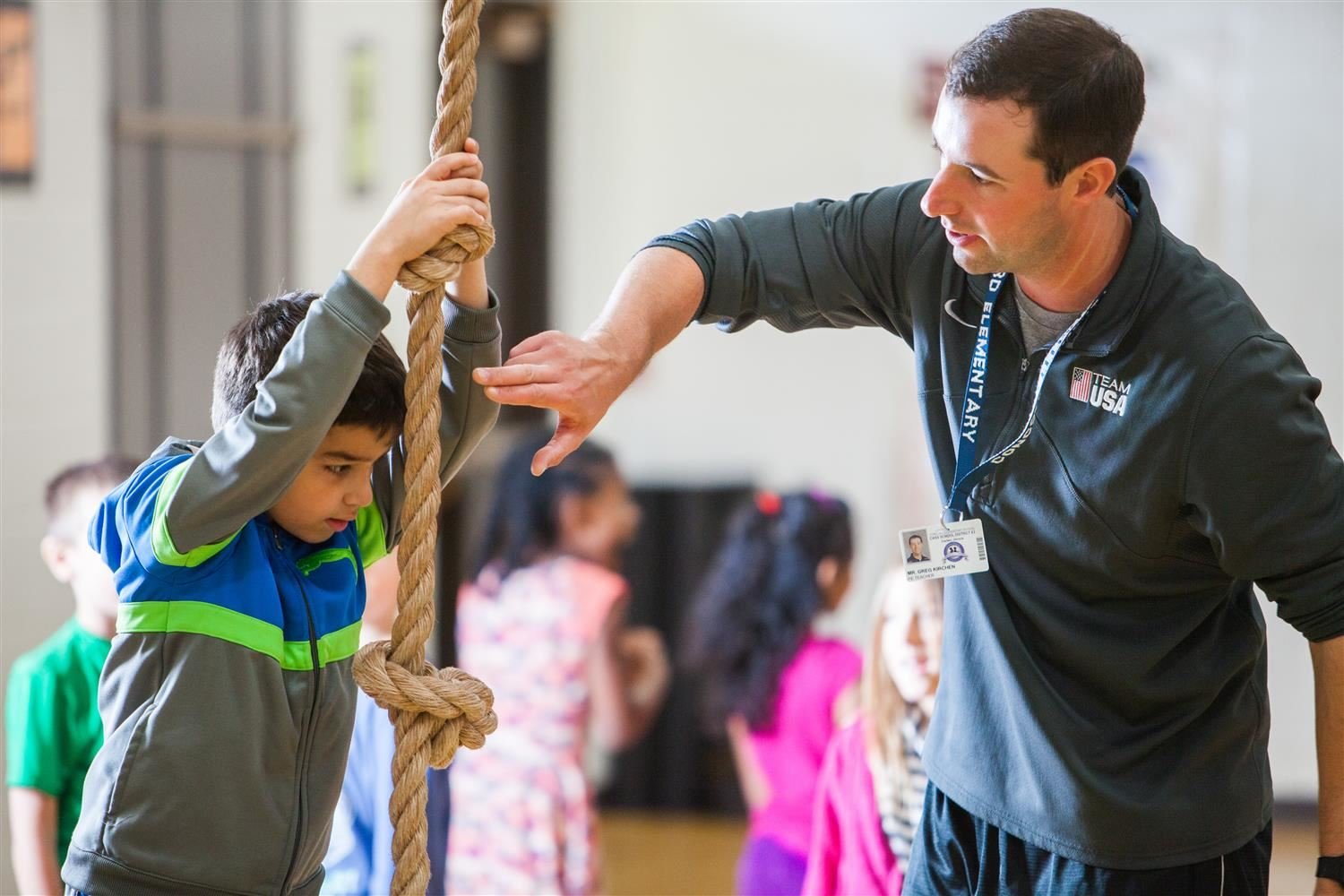 PE teacher and student climbing a rope